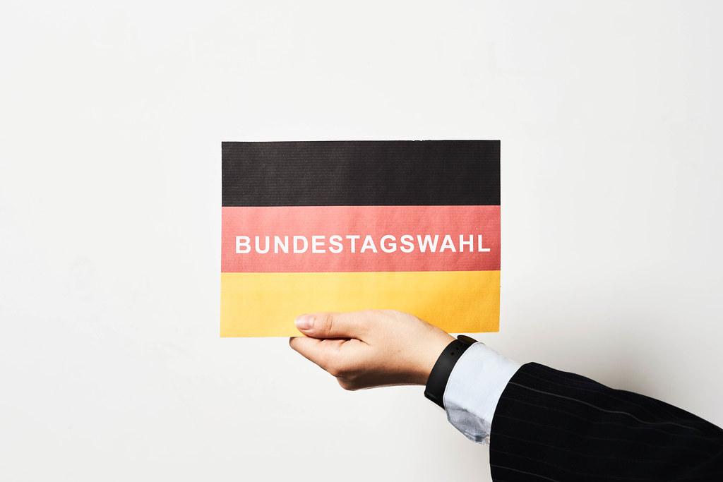"""Hand eines Mannes mit Anzug und Hemd hält eine deutsche Flagge mit Schrift """"Bundestagswahl"""""""