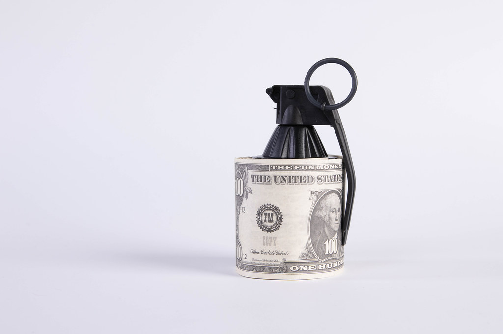 Hand grenade and Dollar banknote on white background