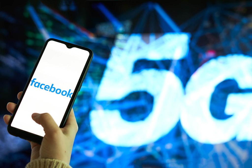 Hand hält ein Smartphone mit dem Facebook Logo auf dem Display und