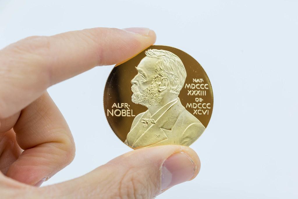 Hand hält Nobelpreis-Goldmedaille mit dem Bild von Alfred Nobel vor weißem Hintergrund