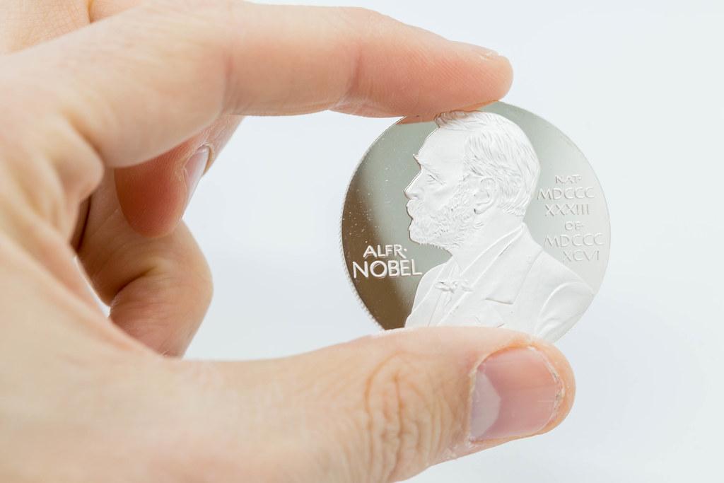 Hand hält silberne Münze mit dem Porträt von Alfred Nobel vor weißem Hintergrund