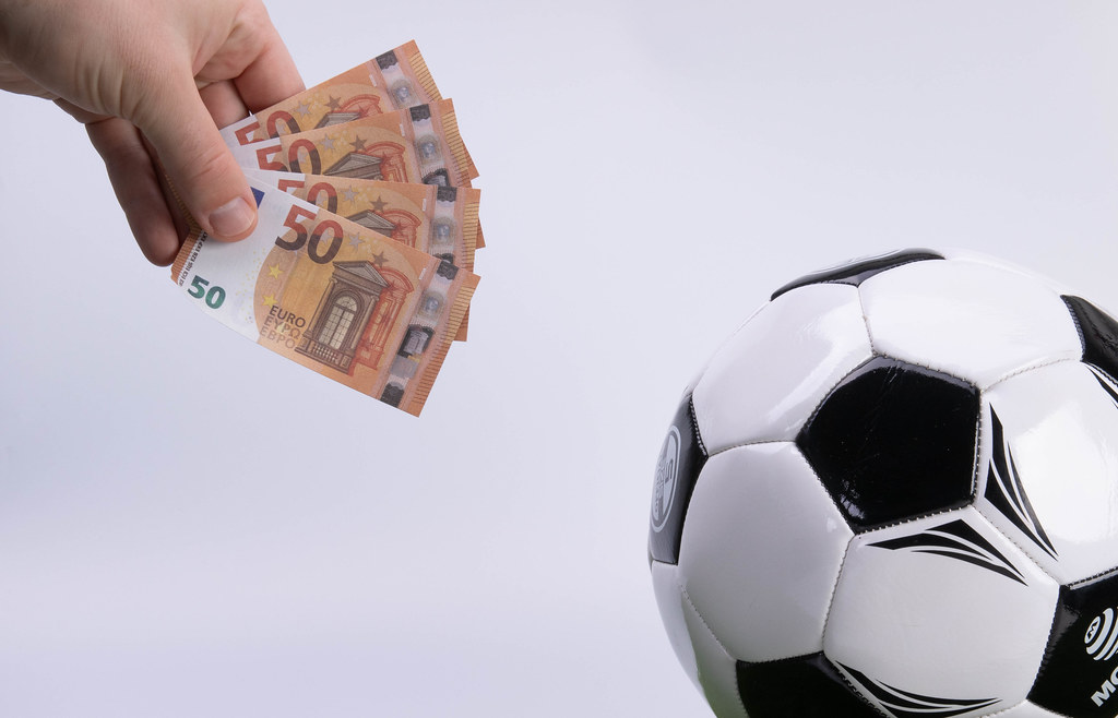 Hand holding 50 Euro banknotes and soccer ball on white background