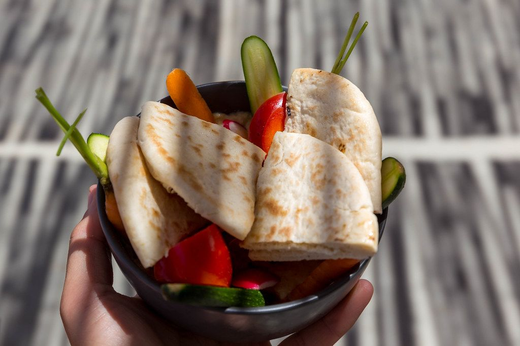 Hand holding a bowl with fresh cut veggies and pita for hummus in the shade