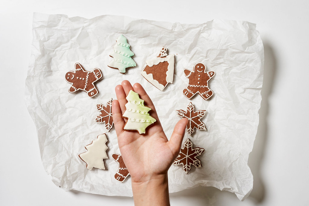Hand holding a freshly baked cookie in form of Christmas tree. Top view