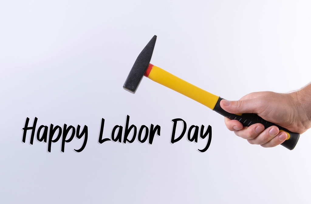 Hand holding a hammer and Happy Labor Day text