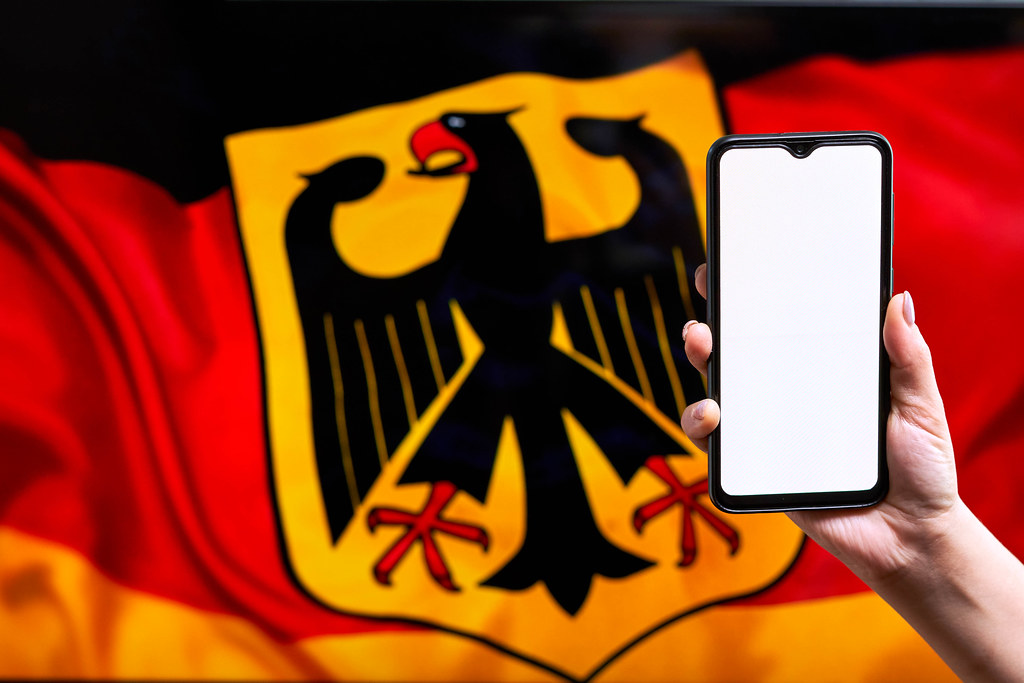 Hand holding a smartphone with a blank screen over the German flag