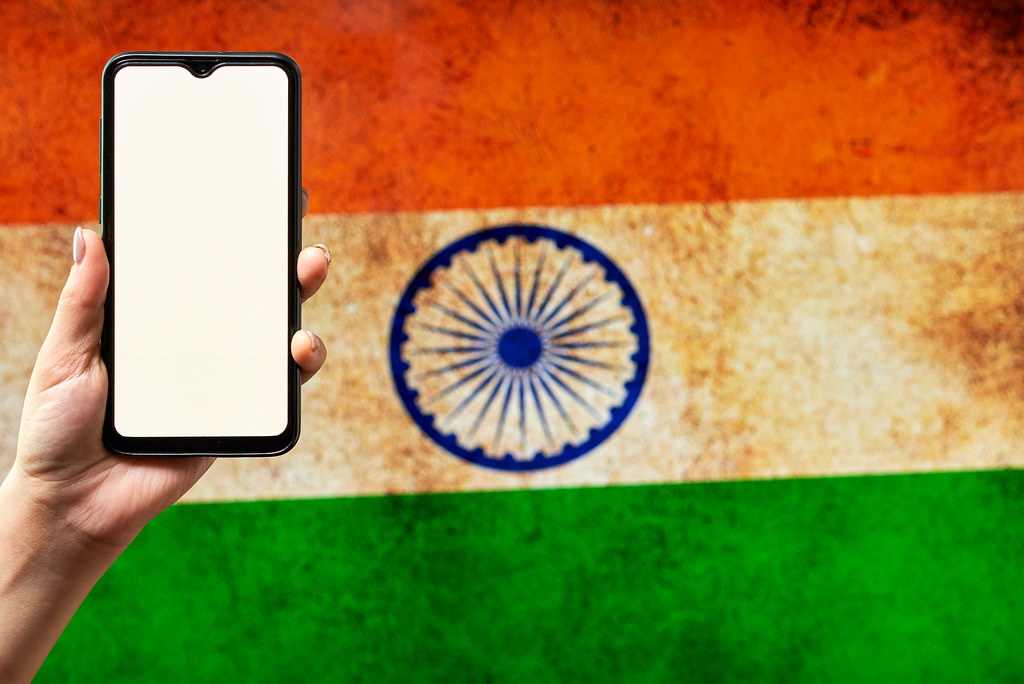 Hand holding a smartphone with a blank screen over the Indian flag