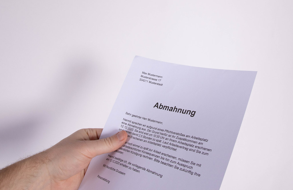 Hand holding Abmahnung document