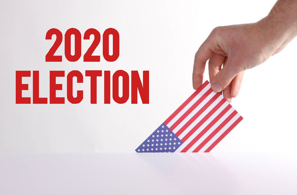 Hand holding American flag with 2020 Election text