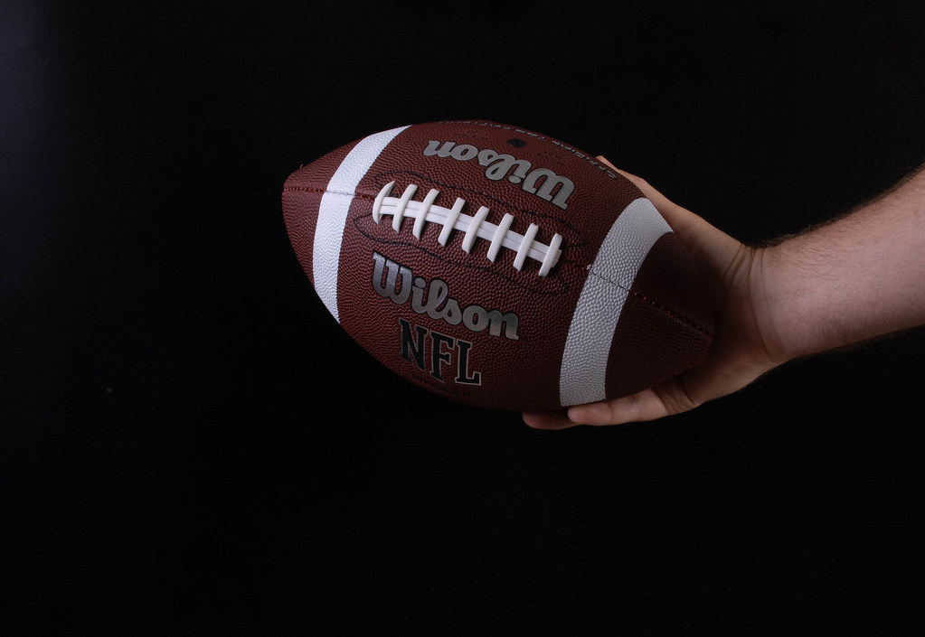 Hand holding american football ball on black background