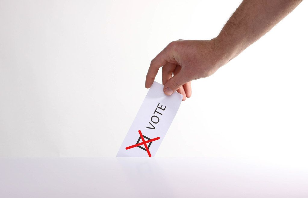 Hand holding ballot paper for election vote concept