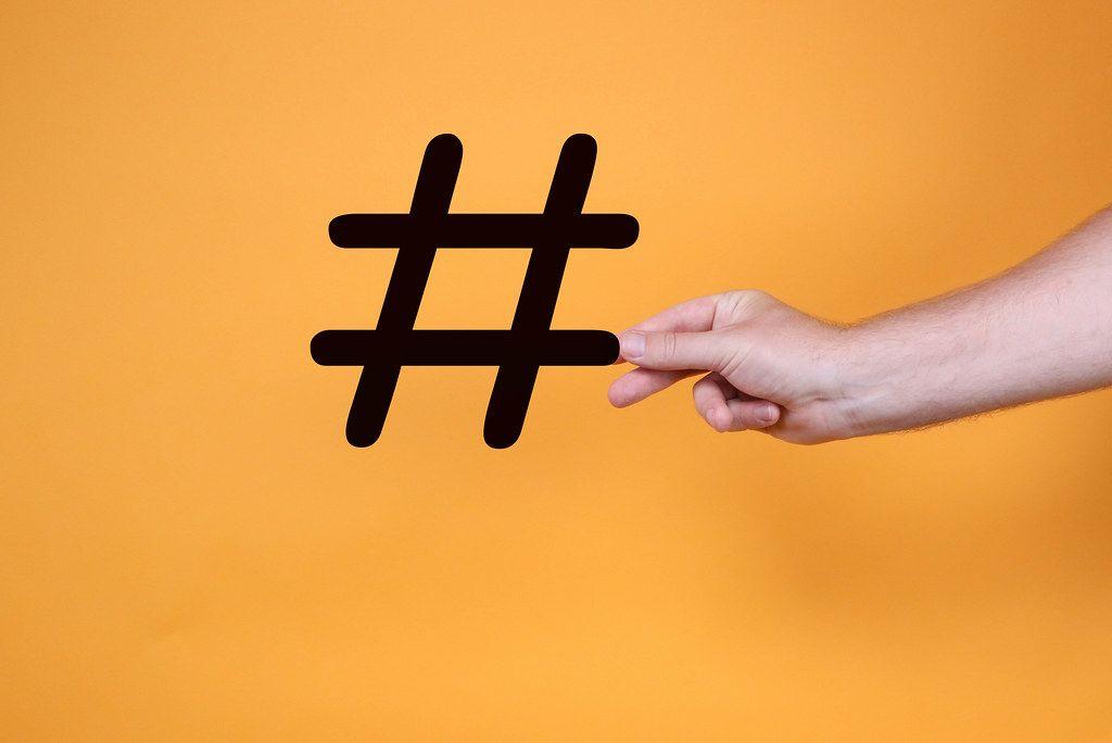 Hand holding big hashtag on orange background