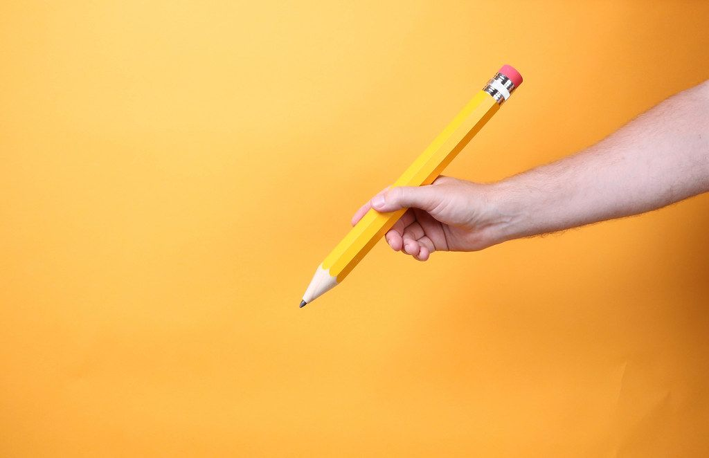 Hand holding big yellow pencil