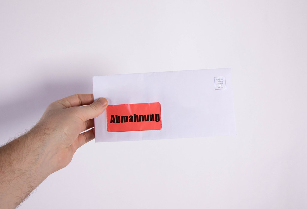Hand holding envelope with Abmahnung text