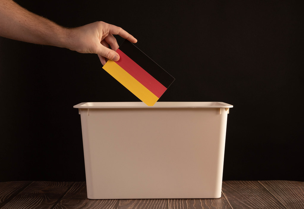 Hand holding German flag over ballout box