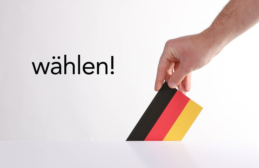 Hand holding German flag with wählen text
