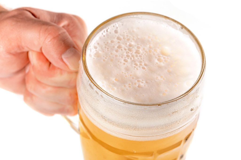 Hand holding glass of beer on a white background, close up