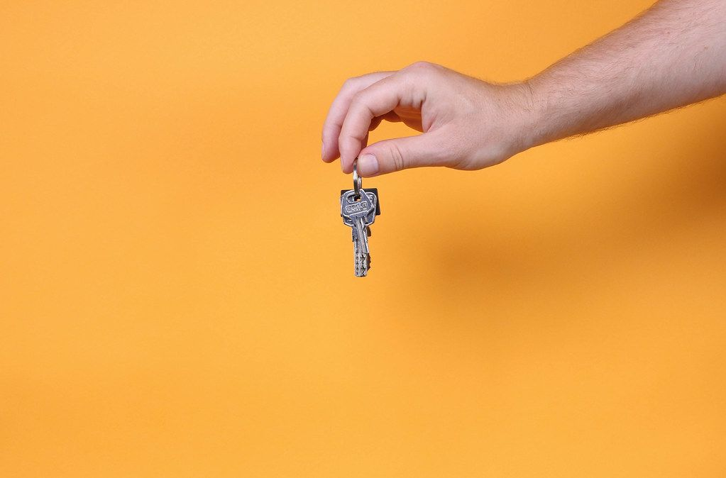 Hand holding keys on orange background