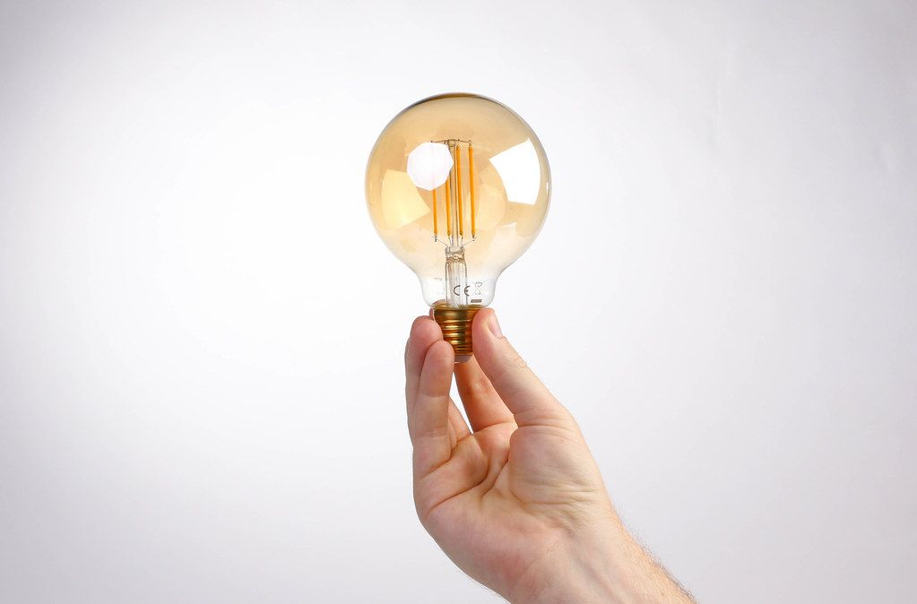 Hand holding lightbulb against white background