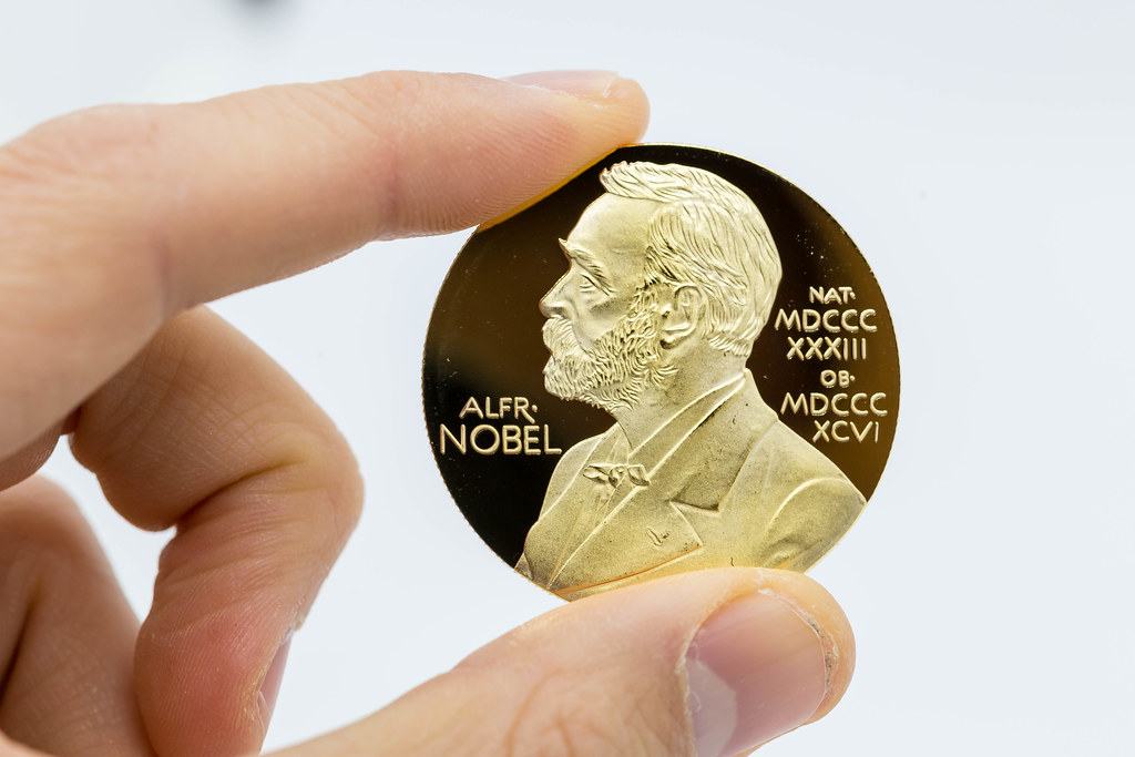 Hand holding Nobel Prize gold medal with the picture of Alfred Nobel against white background
