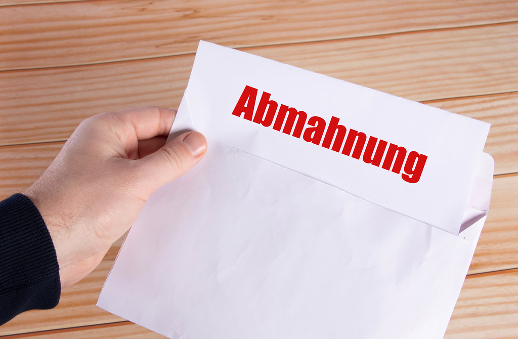 Hand holding open envelope with Abmahnung text