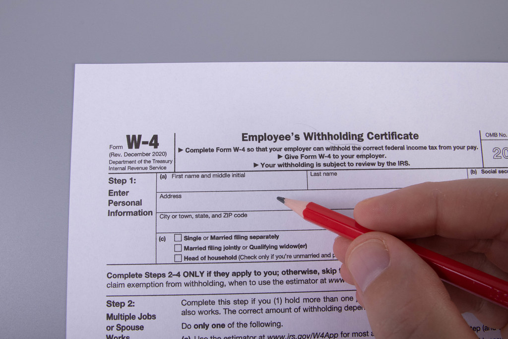 Hand holding pencil and filling out W-4 form