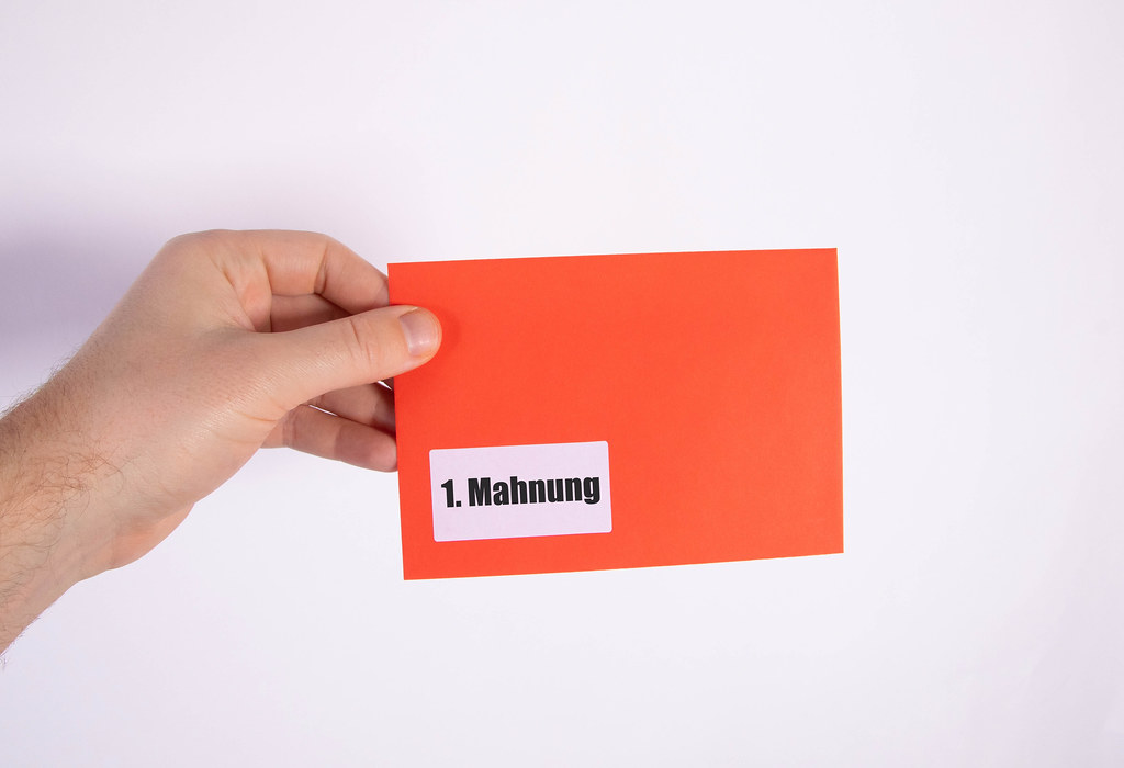 Hand holding red envelope with 1. Mahnung text
