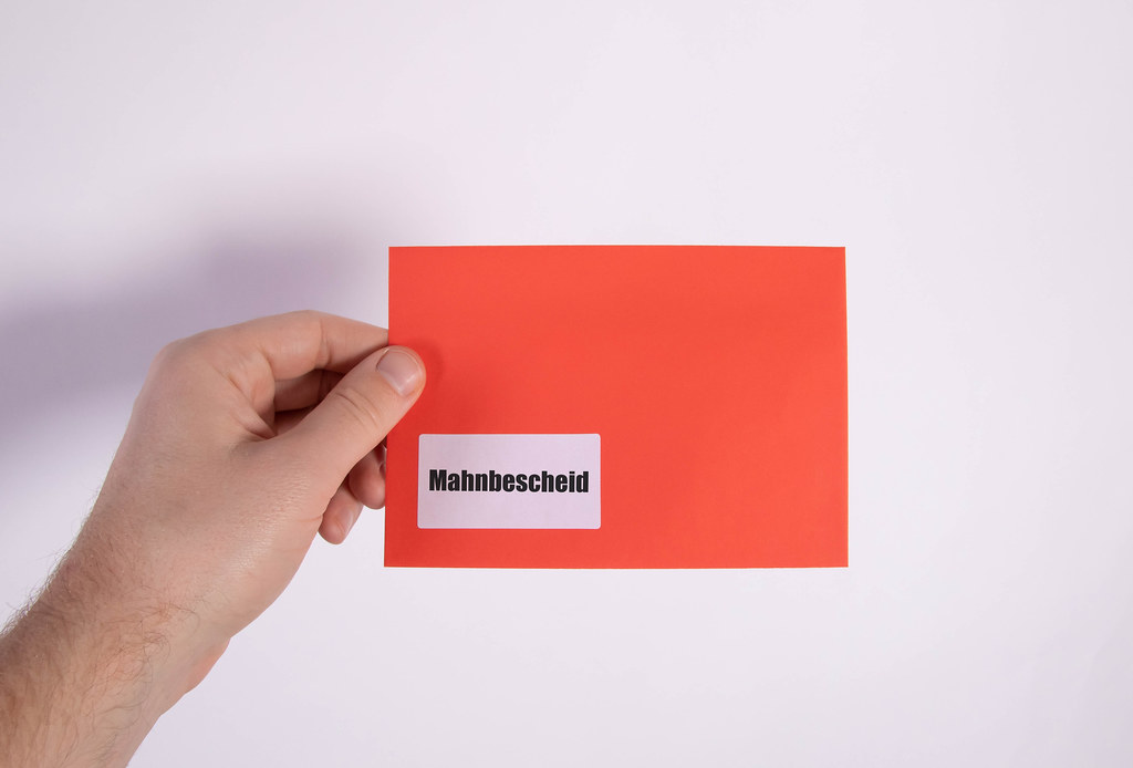 Hand holding red envelope with Mahnbescheid text