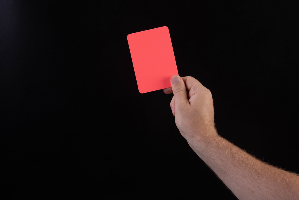 Hand holding red referee card with on black background