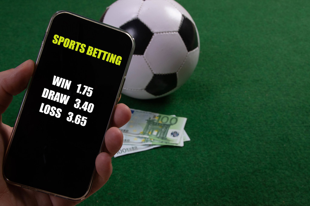 Hand holding smartphone with game betting odds over a soccer ball and Euro banknotes