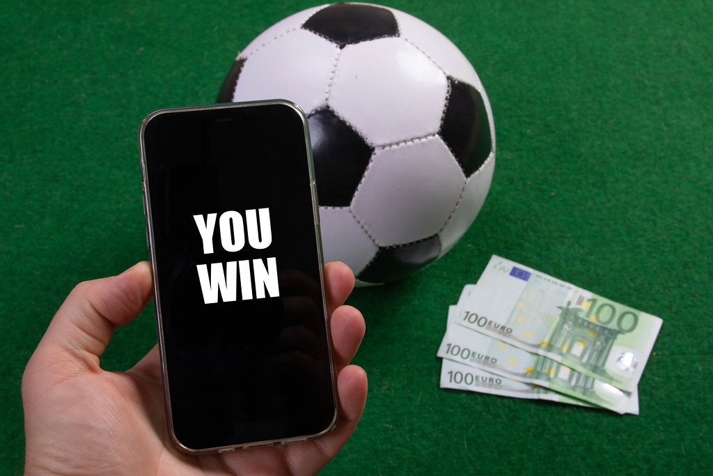 Hand holding smartphone with You Win text over a soccer ball and Euro banknotes
