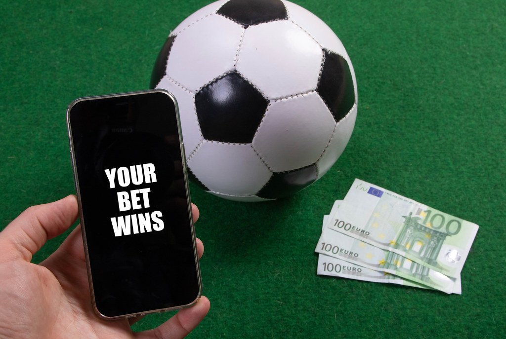 Hand holding smartphone with Your Bet Wins text over a soccer ball and Euro banknotes