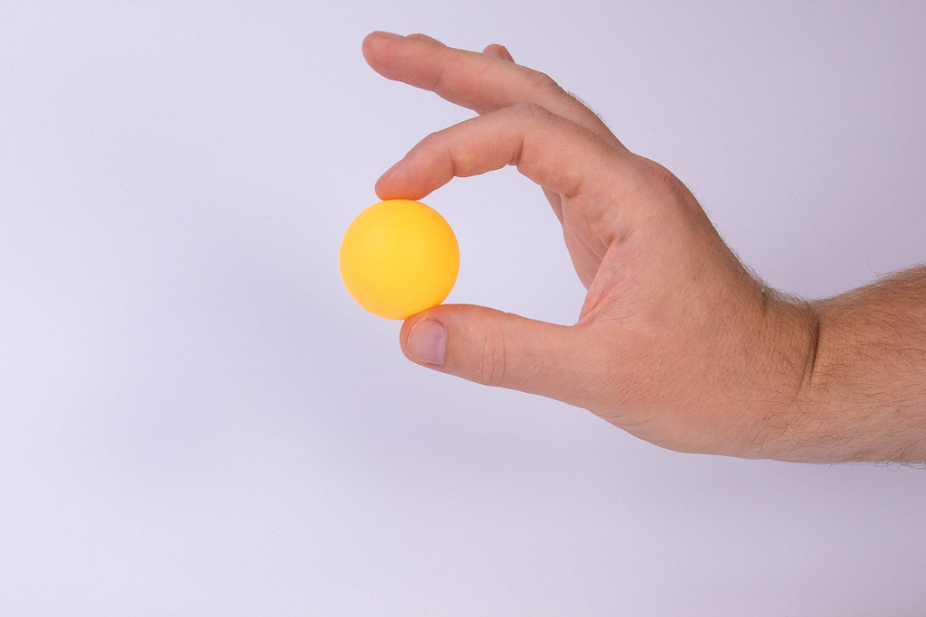 Hand holding table tennis ball on white background