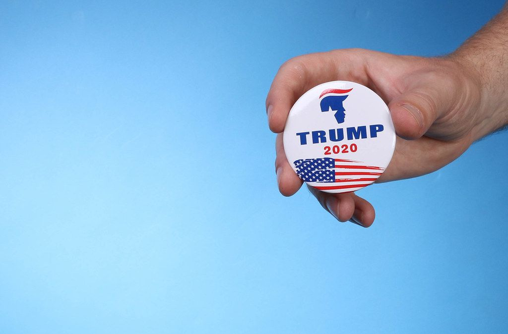 Hand holding Trump 2020 badge