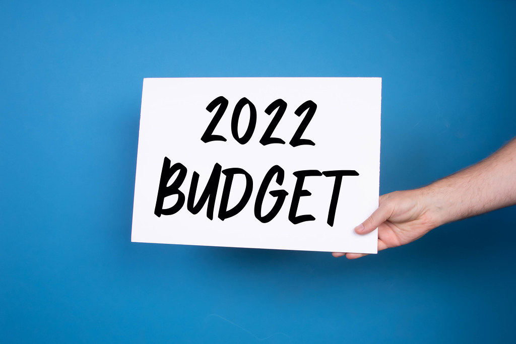 Hand holding white banner with 2022 Budget text on blue background