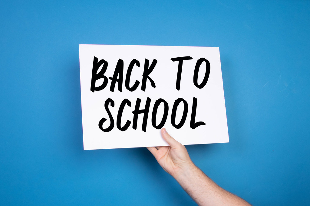 Hand holding white banner with Back to School text on blue background