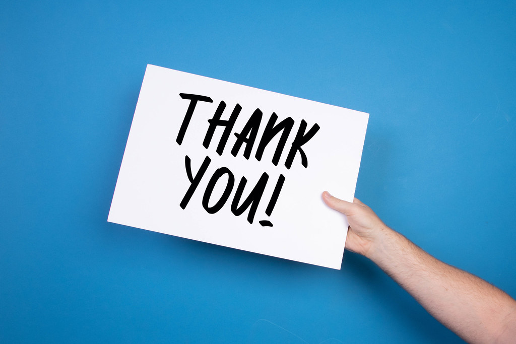 Hand holding white banner with Thank you text on blue background