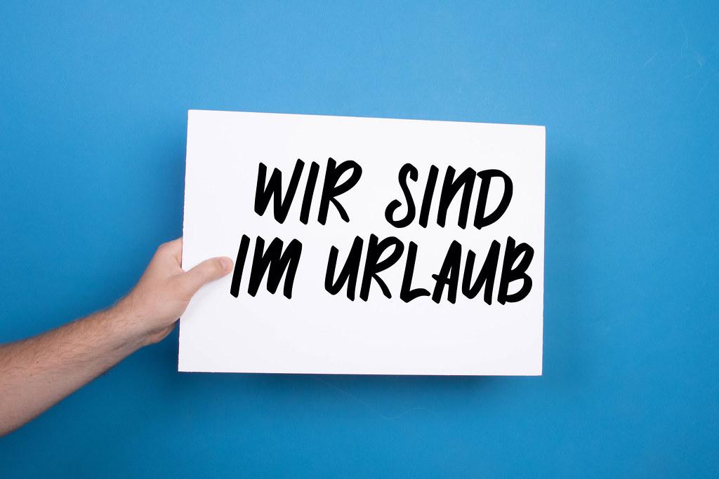Hand holding white banner with Wir Sind Im Urlaub text on blue background