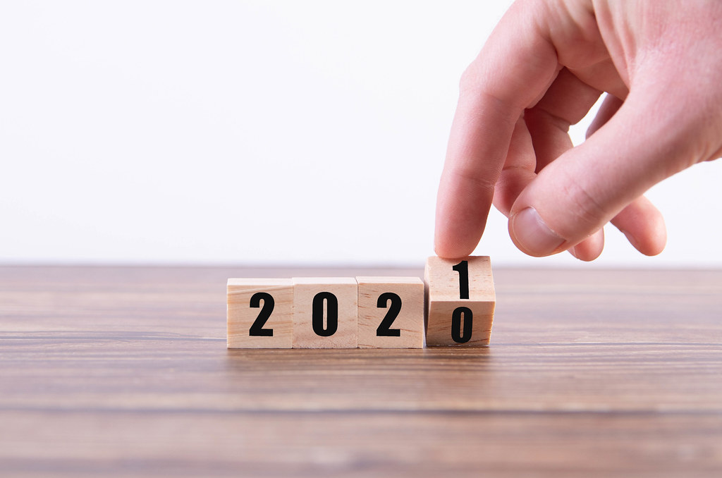 Hand holding wooden cube with flip over block 2020 to 2021