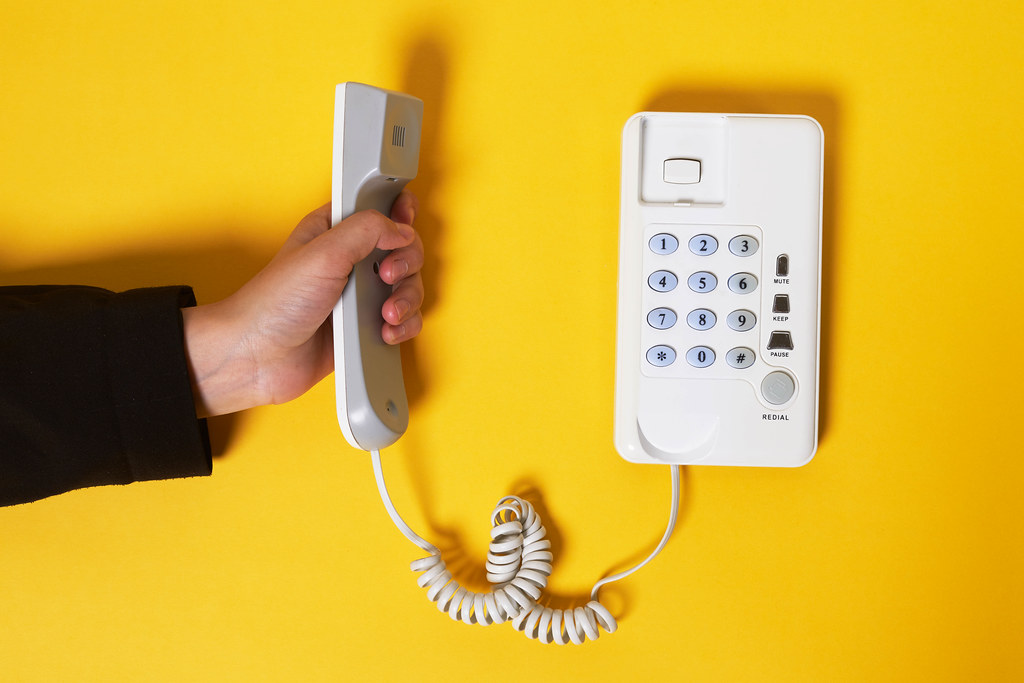 Hand holds classic telephone handset over bright yellow background