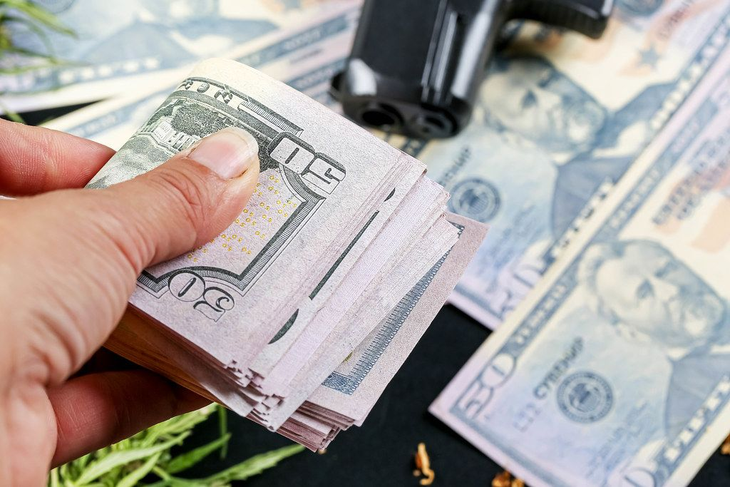 Hand holds money on the background of a gun and dollars