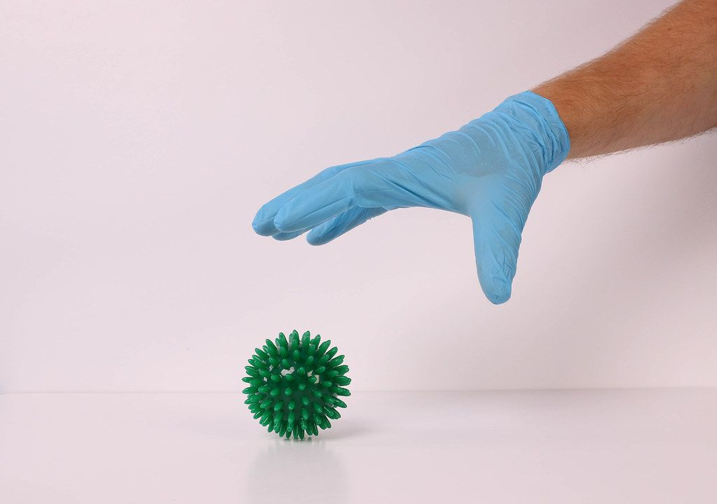 Hand in medical glove catching coronavirus bacteria