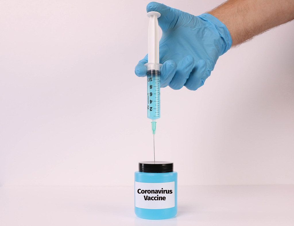 Hand in medical gloves holding syringe over bottle with Coronavirus Vaccine text