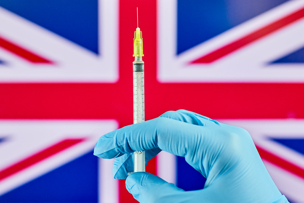 Hand in medical gloves holds syringe with vaccine over the Great Britain flag