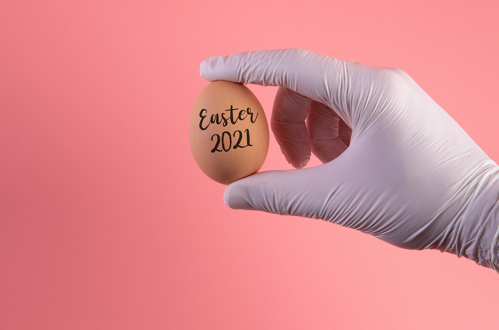 Hand in protective gloves holding egg with Easter 2021 text