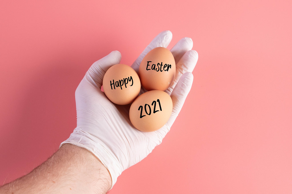 Hand in protective gloves holding eggs with Happy Easter 2021 text