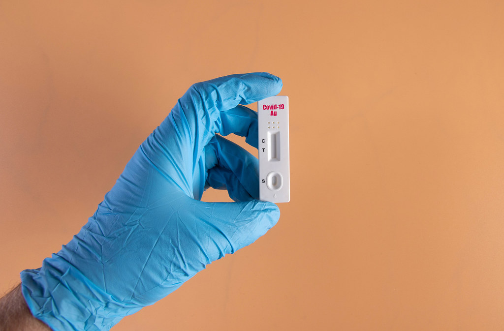 Hand in protective gloves holding rapid antigen test for Covid-19