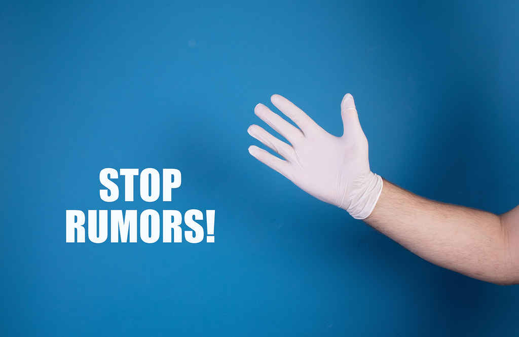 Hand in white protective gloves with Stop rumors text
