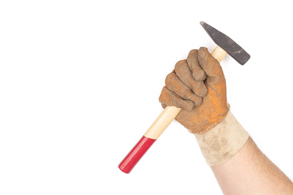 Hand in work gloves with hammer above white background with copy space