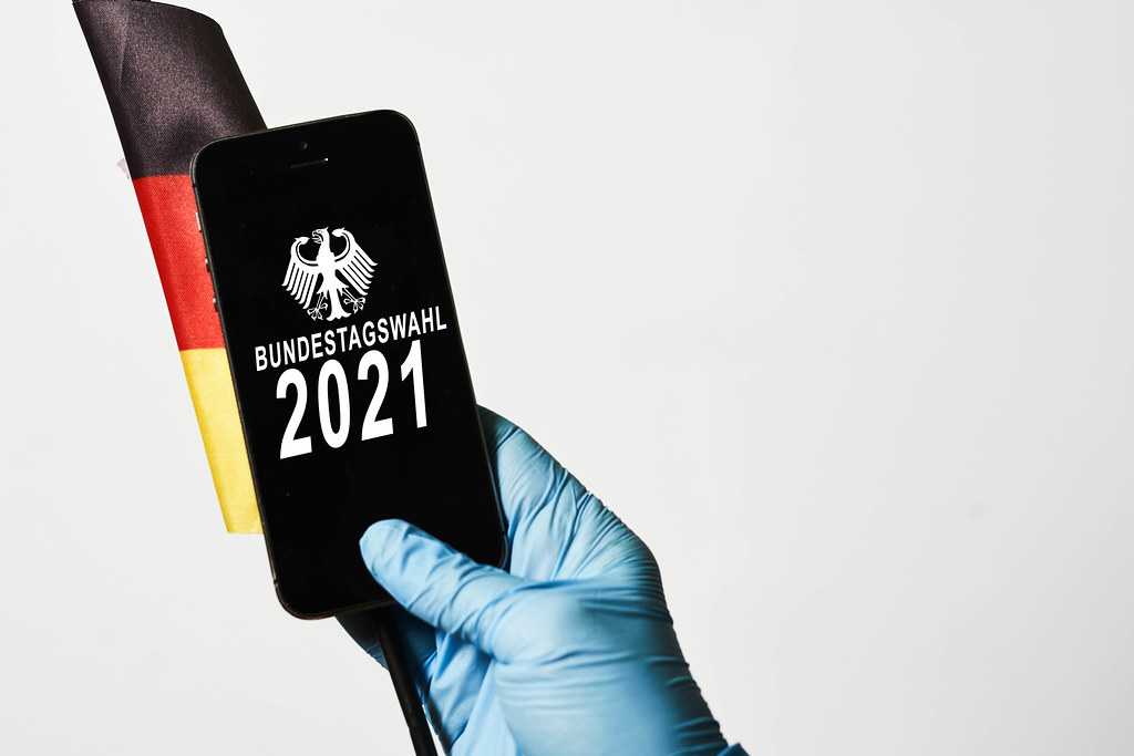 """Hand mit Einmalhandschuh hält Smartphone mit Schrift """"Bundestagswahl 2021"""" vor der deutschen Flagge"""